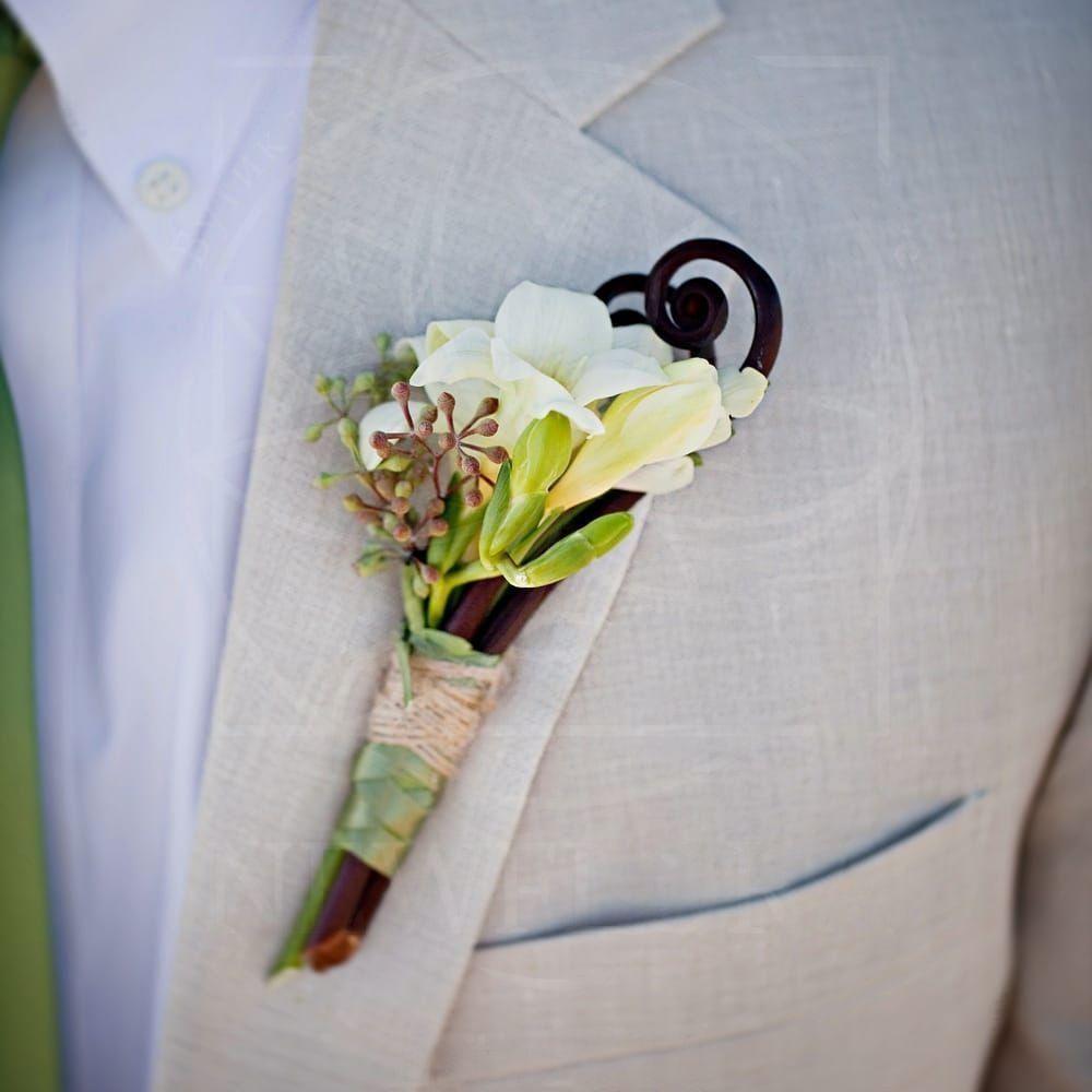 Бутоньерка состоит из вайи папоротника, фрезии и эвкалипта