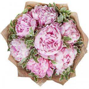 Букет 7 больших розовых пионов с зеленью в крафт бумаге