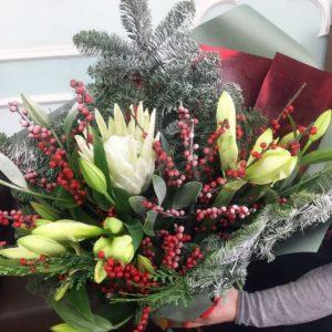 Зимний букет амариллисов с белой протеей, лилиями, илексом и лапником пихты