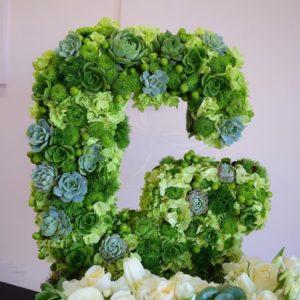 Буква «G» из живых цветов на подставке