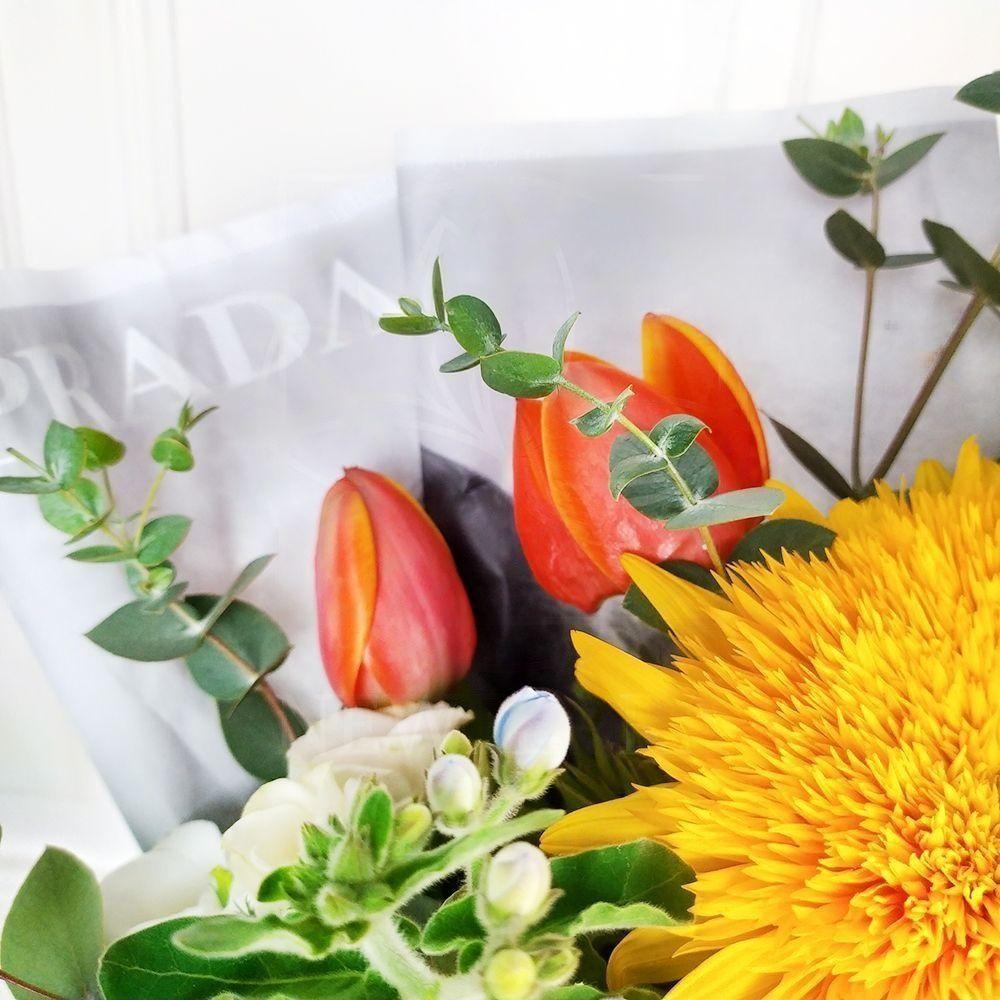 Букет кустовых роз с оксипеталум и подсолнухом в упаковке PRADA